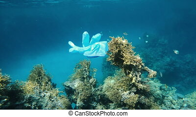 Virus. The medical protective glove floats in the sea.