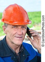 visão close-up, de, maduras, trabalhador manual, em, laranja, hardhat, chamando, telefone