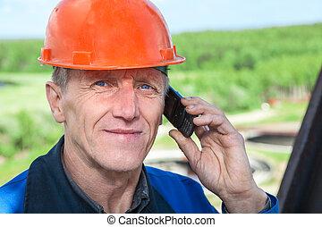 visão close-up, de, sênior, trabalhador manual, em, laranja, hardhat, chamando, telefone