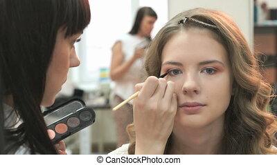 Visage master making make-up for young model - Professional...