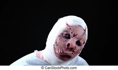 visage of a patient with a disfigured face, a sewn-in mouth and a bandaged head. A hero from a horror movie or an costume for Halloween. Profassional make up