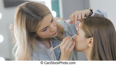 Visagist is applying shadows on woman's eyelids using brush. Professional makeup artist doing makeup on eyes for young model in beauty salon. Fashion, glamour, beauty industry.