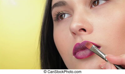 Visagist paints lips of brunette girl