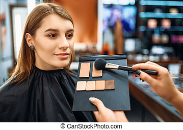 Visagiste and lady chooses cosmetic in makeup shop