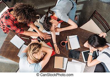 visión de arriba, de, cansado, joven, estudiantes, sueño, en, tabla, con, cuadernos, y, digital, dispositivos