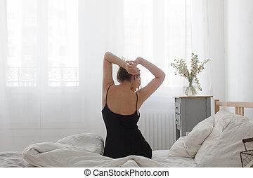 visión trasera, de, mujer se sentar, cama, en, el, mañana