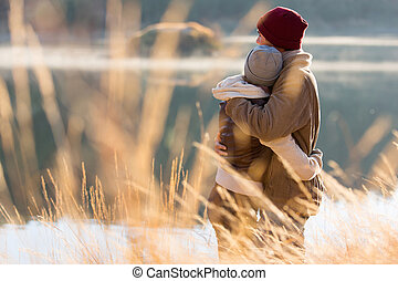 visión trasera, de, pareja joven, abrazar, en, invierno