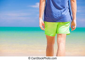visión trasera, de, un, hombre caminar, en, playa