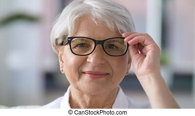 portrait of happy senior woman in glasses - vision, age and...