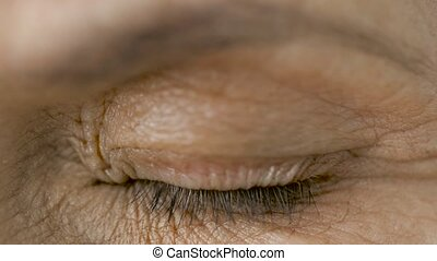 close up of blinking senior woman eye - vision and old...