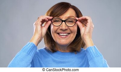 portrait of happy senior woman putting glasses on - vision,...