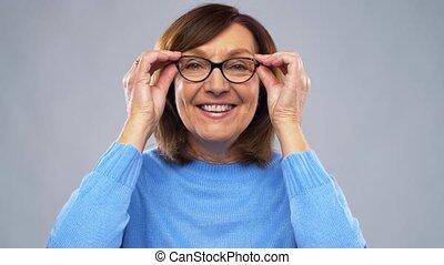 portrait of happy senior woman putting glasses on - vision,...