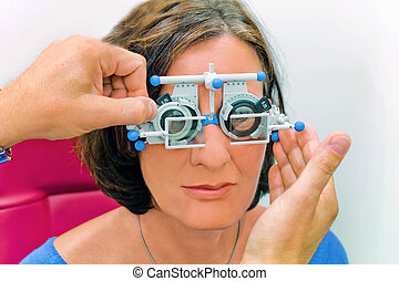 vision test at the optician / eye doctor - a woman makes an...