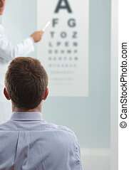 Vision Test - Optometrist and patient, doctor pointing at...