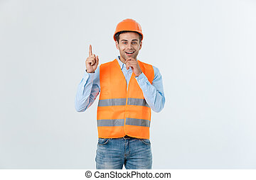 Visionary architect or engineer looking up and thinking about new projects. Wearing yellow hardhat and reflective vest isolated on white background.
