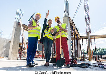 Visionary architect pointing up while guiding and motivating wor