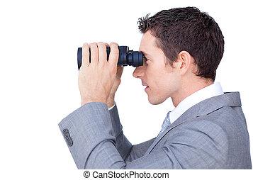 Visionary businessman looking through binoculars against a ...