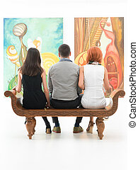 back view of three young people sitting on a wooden bench in a museum admiring large paintings