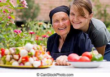 A young woman - grandchild or carer - next to an old woman at the table, with fresh food in front of them.