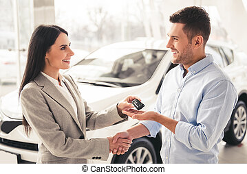 Visiting car dealership. Handsome man is getting car key from beautiful sales manager, shaking her hand and smiling
