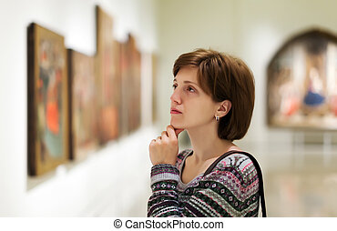 visitor looking pictures in art gallery - Female visitor...