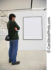 Visitor looks on frame in showroom