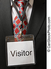 businessman wearing a visitor identification badge around his neck