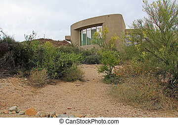 Visitors center for Saguaro National Park, Tucson, Arizona, as seen from the back side from within the park looking past various desert plants.