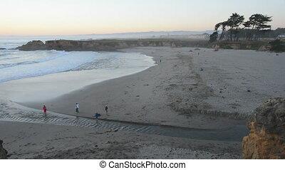Visitors walk along the beach at sunset