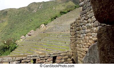 Visitors walking along Machu Picchu terraces, Peru - Wide...