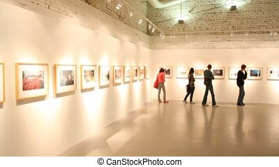 visitors walks and looks at pictures in exhibition hall