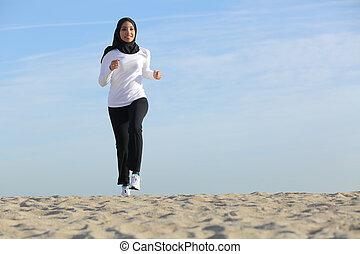 vista delantera, de, un, árabe, saudí, emiratos, mujer que corre, en la playa