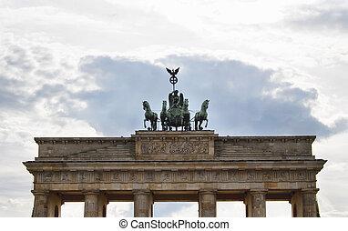 vista inferiora, de, branderburg, puerta, con, cielo nublado, plano de fondo, en, berlin., restaurado, 18th-century, puerta, y, señal, con, 12, dórico, columnas, rematado, por, un, clásico, diosa, statue.