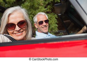 vista lateral, de, alegre, pareja madura, conducción, rojo, cabriolet