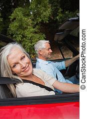 vista lateral, de, feliz, pareja madura, conducción, rojo, cabriolet