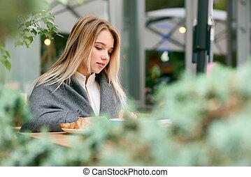 vista lateral, de, jovem, loiro, leitura menina, livro, sentando, coberto, com, blanket.