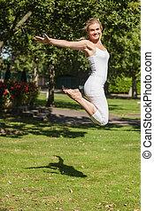 vista lateral, de, joven, alegre, mujer, saltar, esparcimiento, ella, brazos