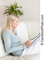 vista lateral, de, leitura mulher, ligado, dela, sofá