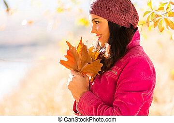 vista lateral, de, mujer joven, tenencia, otoño sale