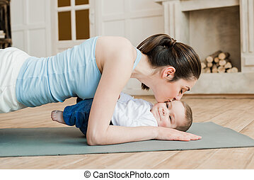 vista lateral, de, mulher, fazendo, prancha, exercício, e, beijando, dela, filho