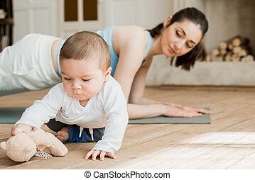 vista lateral, de, mulher, fazendo, prancha, exercício, enquanto, dela, filho, tocando, com, urso teddy