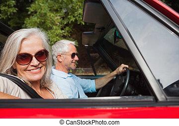 vista lateral, de, sonriente, pareja madura, conducción, rojo, cabriolet