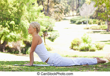 vista lateral, de, un, mujer, hacer, estira, en la hierba