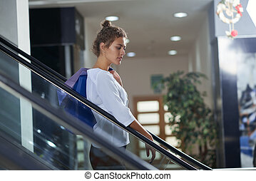 vista laterale, di, elegante, donna, inclinandosi, ringhiera, di, scala mobile, in, centro commerciale