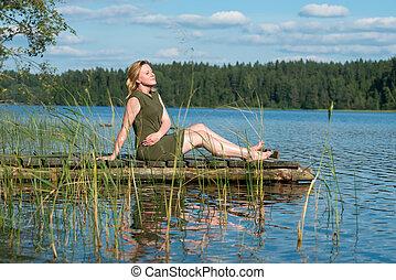 vista laterale, di, sognare, ragazza, seduta, su, molo, foresta, e, fiume, su, fondo., bella donna, seduta, vicino, il, lake.
