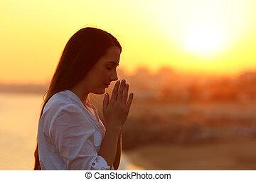 vista laterale, di, uno, donna pregando, a, tramonto