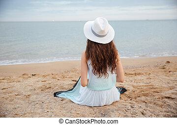 vista posteriore, di, giovane, sedendo spiaggia