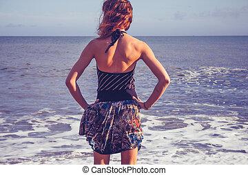 vista posteriore, di, giovane, standing, su, spiaggia, mare guardare