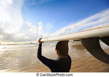 vista posteriore, di, giovane, surfer, con, bianco, surfboard, su, uno, spiaggia, a, alba