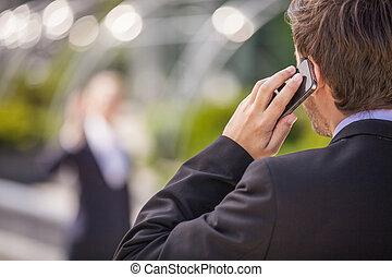 vista posteriore, di, uomo affari, in, black., giovane, comunicando telefono mobile